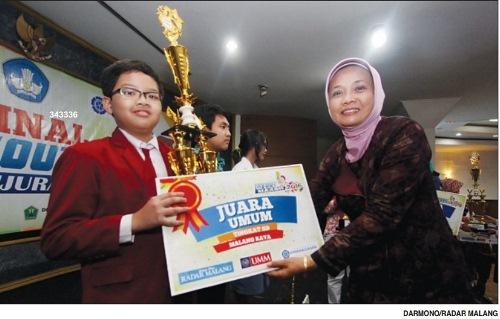 SELAMAT YA..: Muhammad Shabri menerima trofi dari Kabid Sekolah Menengah Disdik Kabupaten Malang Puji Hariwati di Dome UMM, Minggu 20/3/2016 lalu.